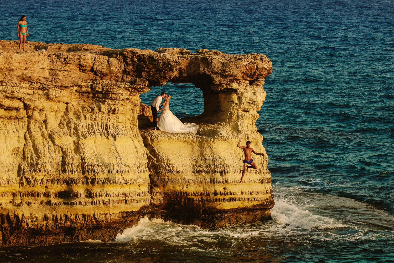 Man jumping off cliff with bride and groom in hole sea caves in Cyprus