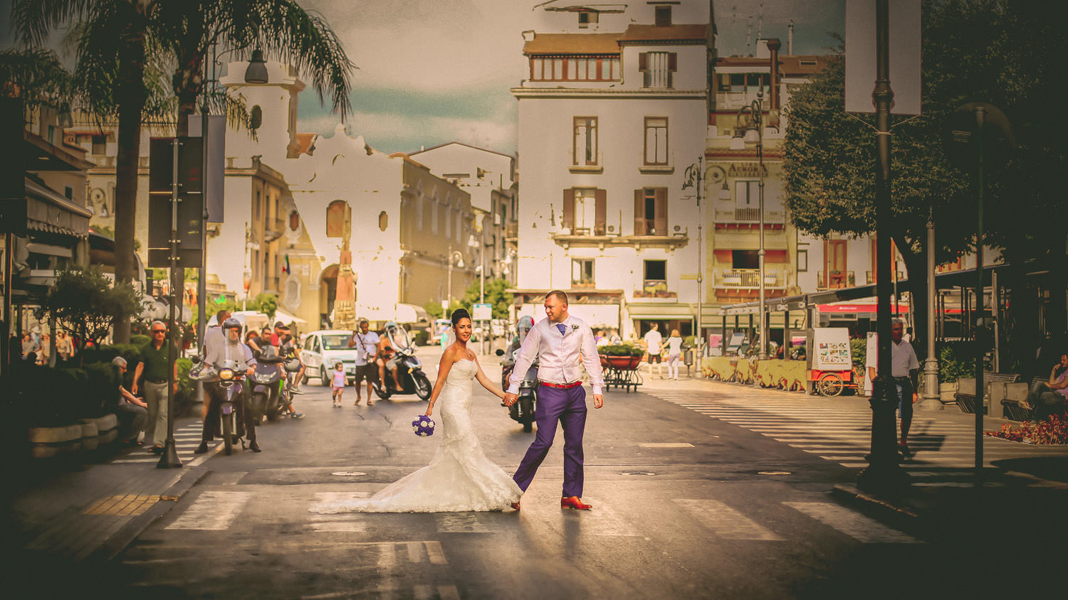 Bride and groom crossing busy road in Sorrento