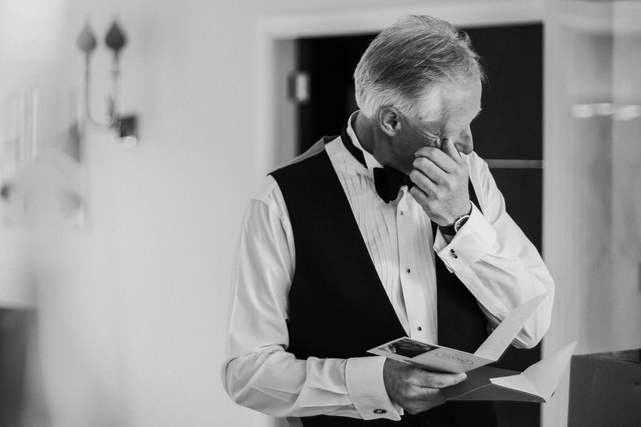 Father of bride wiping tear as her ears card