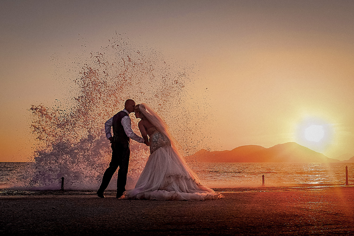 Big wave crashing over bride and groom at sunset wedding photography at Liberty Hotels Lykia