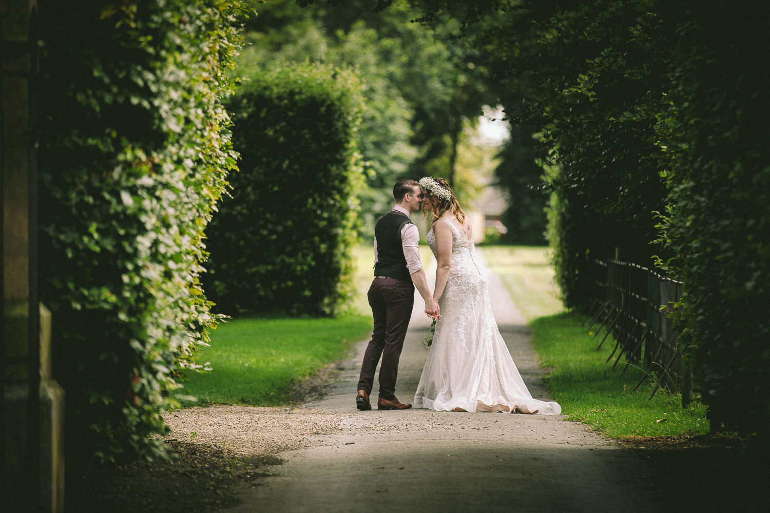 Bide and groom kissing on path at Meols hall