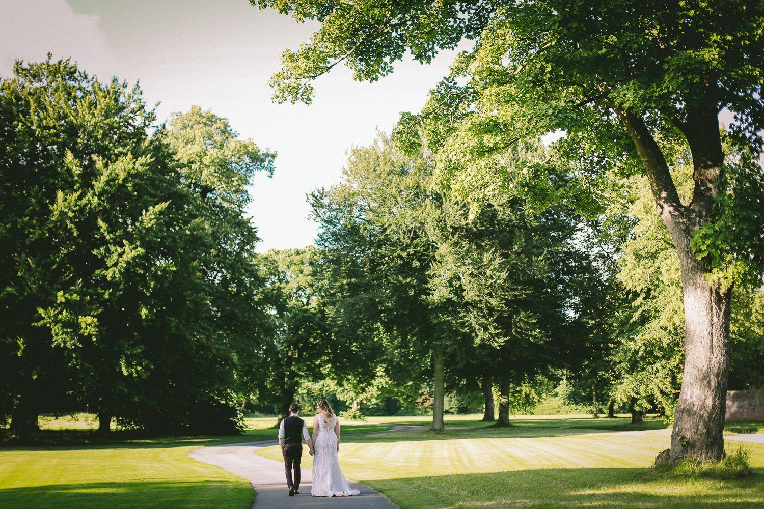 Bride and groom walking down path Rustic wedding at Meols Hall Southport