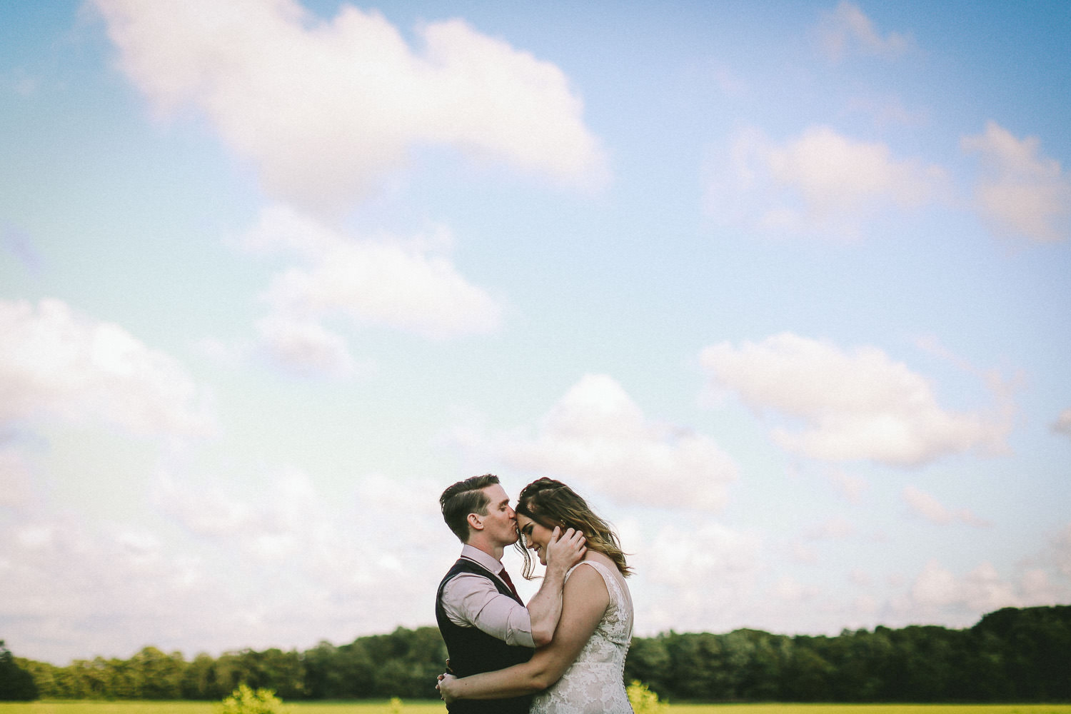 Groom kissing bride on head with blue skies Rustic wedding at Meols Hall Southport