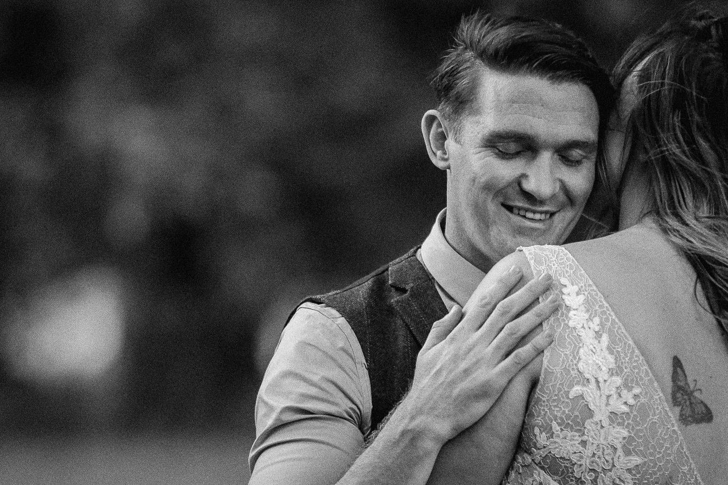 Black and white photo of groom hugging bride, Rustic wedding at Meols Hall Southport