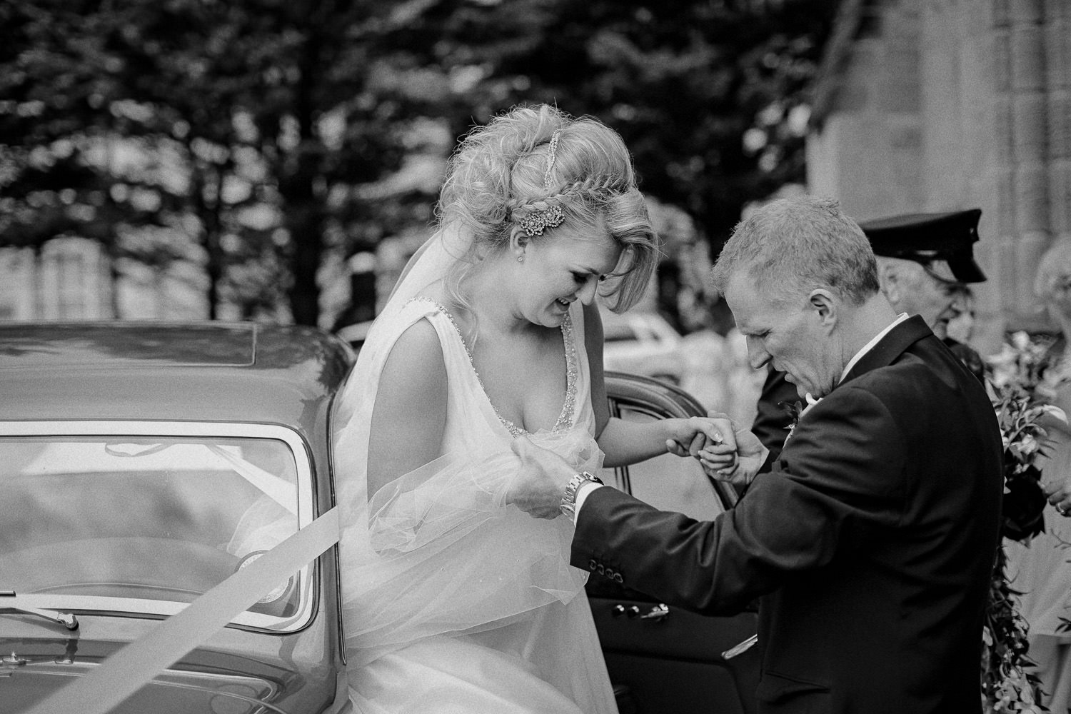 Dad helping daughter out of Roll Royce wedding car