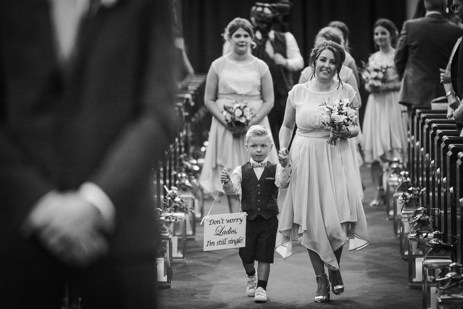 Little page boy walking down the aisle with sign saying 'Don't worry ladies I'm still single""