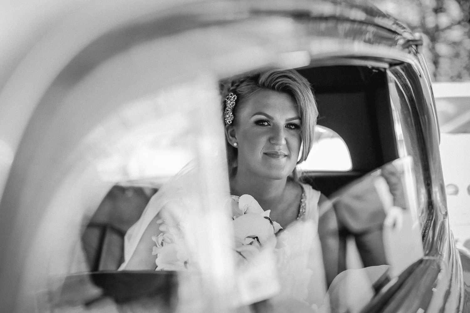 Black and white photo of bride through Rolls Royce wedding car window