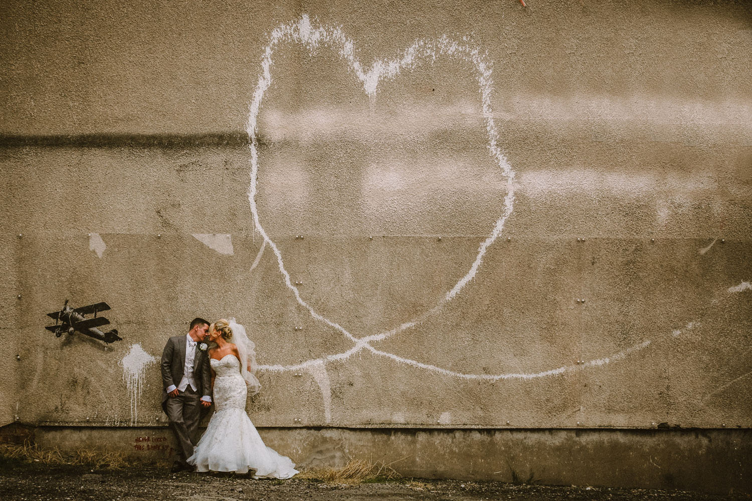 Bride and Groom with Banksy love plane. Top 10 wedding venues in Liverpool