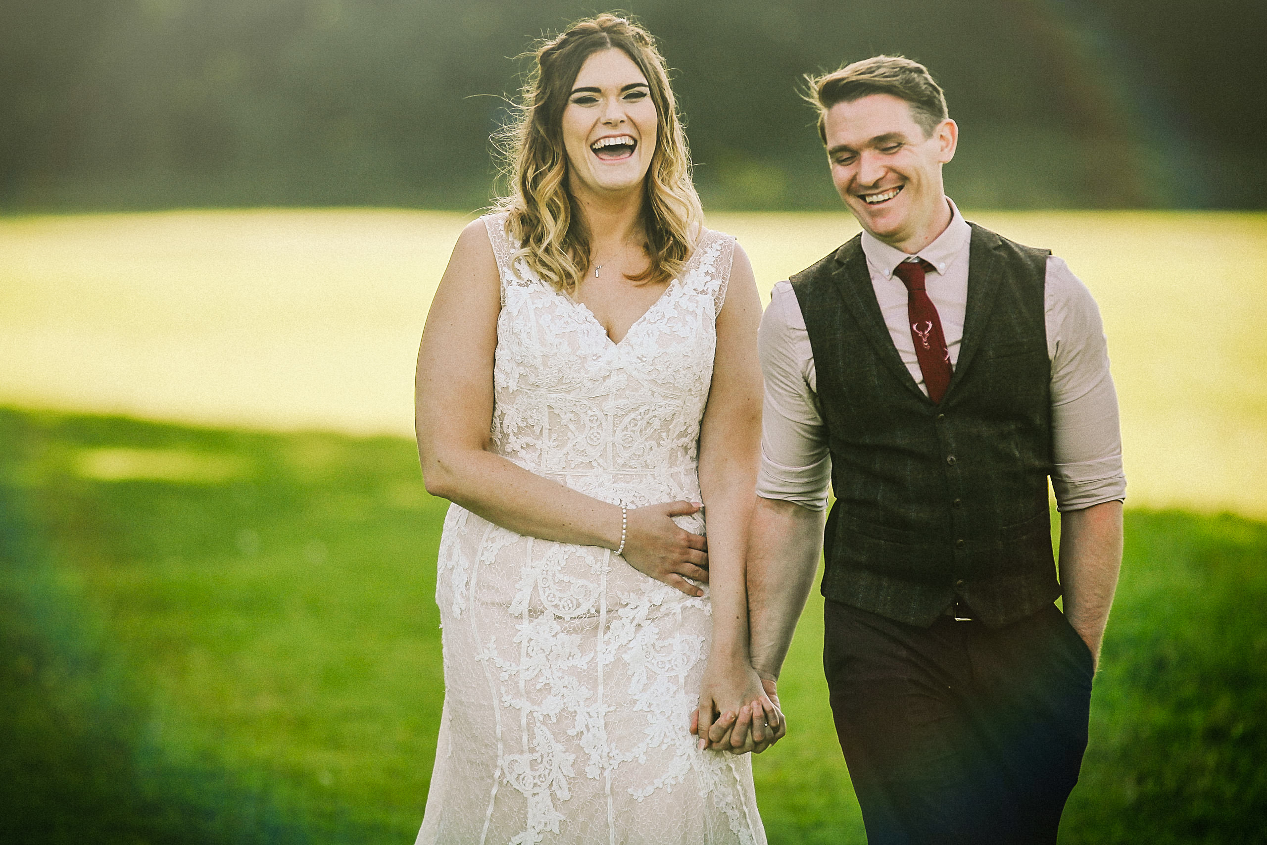 Bride and groom laughing walking outside during Rustic wedding at Meols Hall Southport