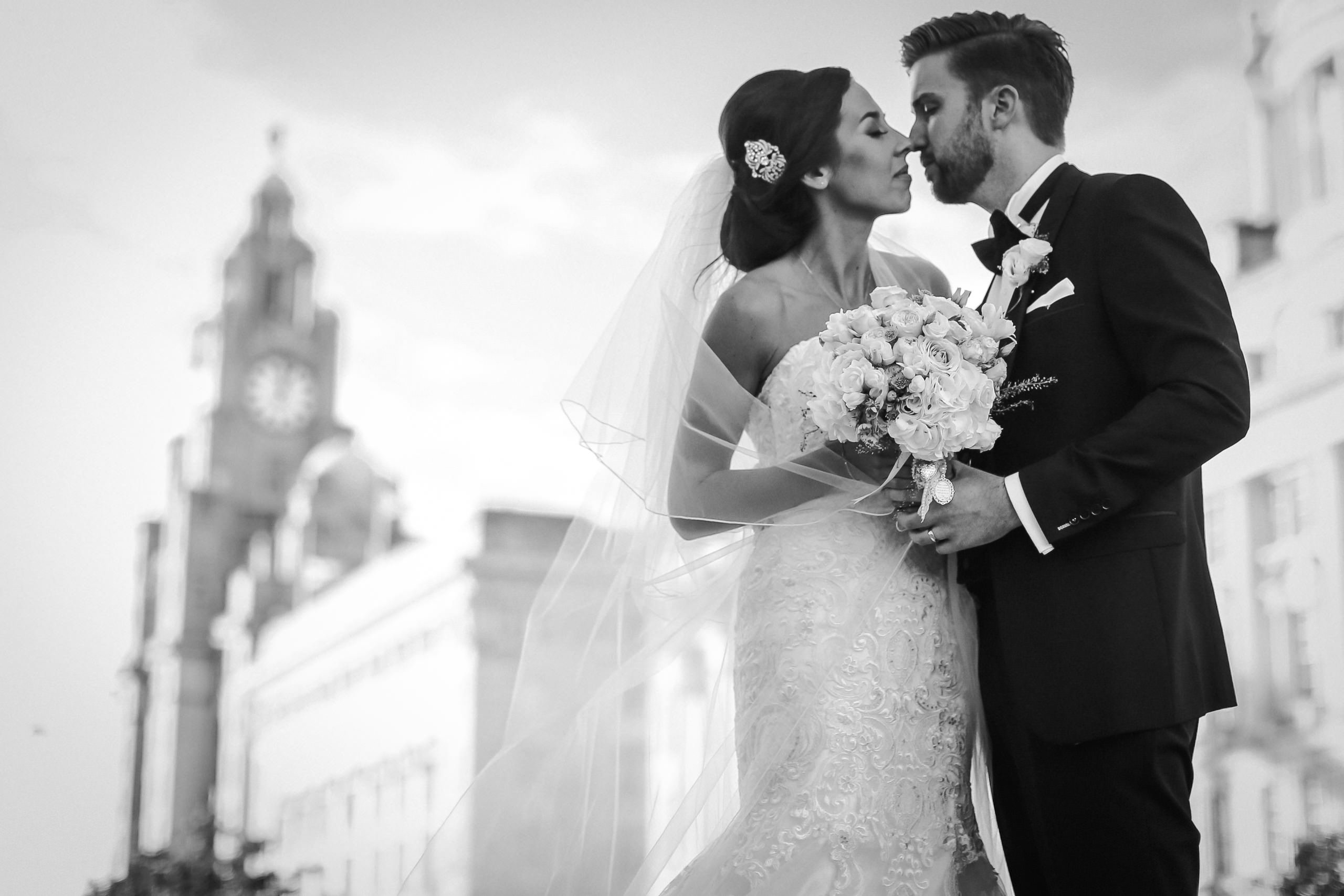 Black and white photo of bride and groom about to kiss with Liver Building in the background. Top 10 wedding venues in Liverpool