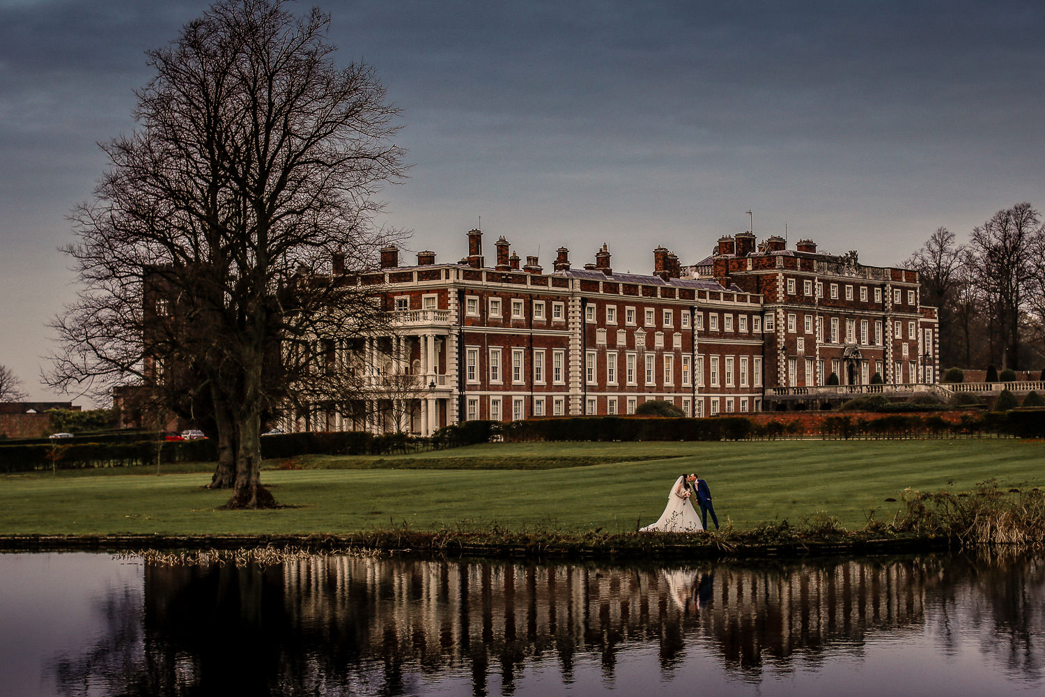 Panoramic photo of bride and groom reflection on lake with Knowsley Hall in background. Top 10 wedding venues in Liverpool