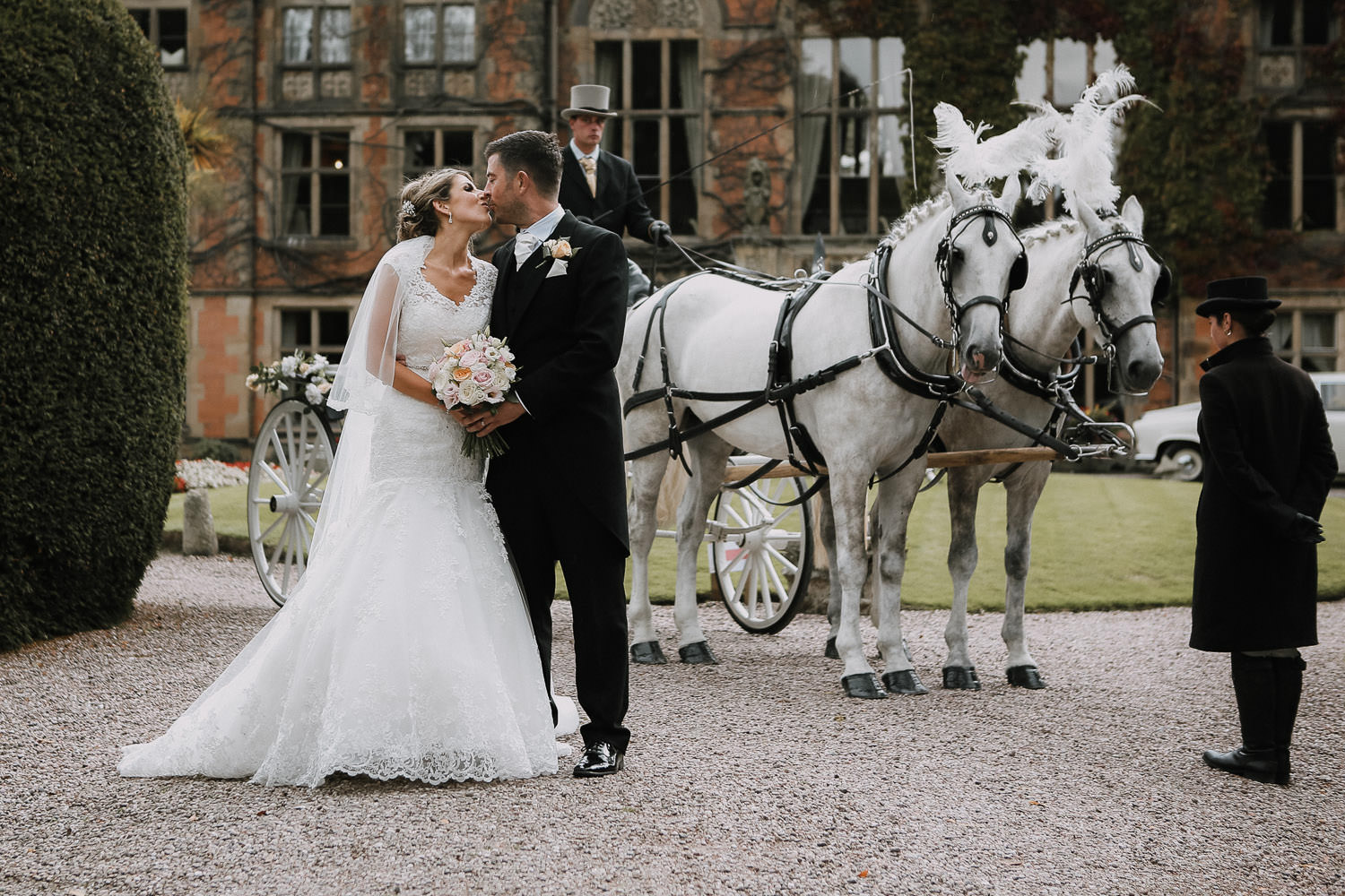 Bride and groom kissing in front of horse and kart at Soughton Hall Top 10 wedding venues in Liverpool