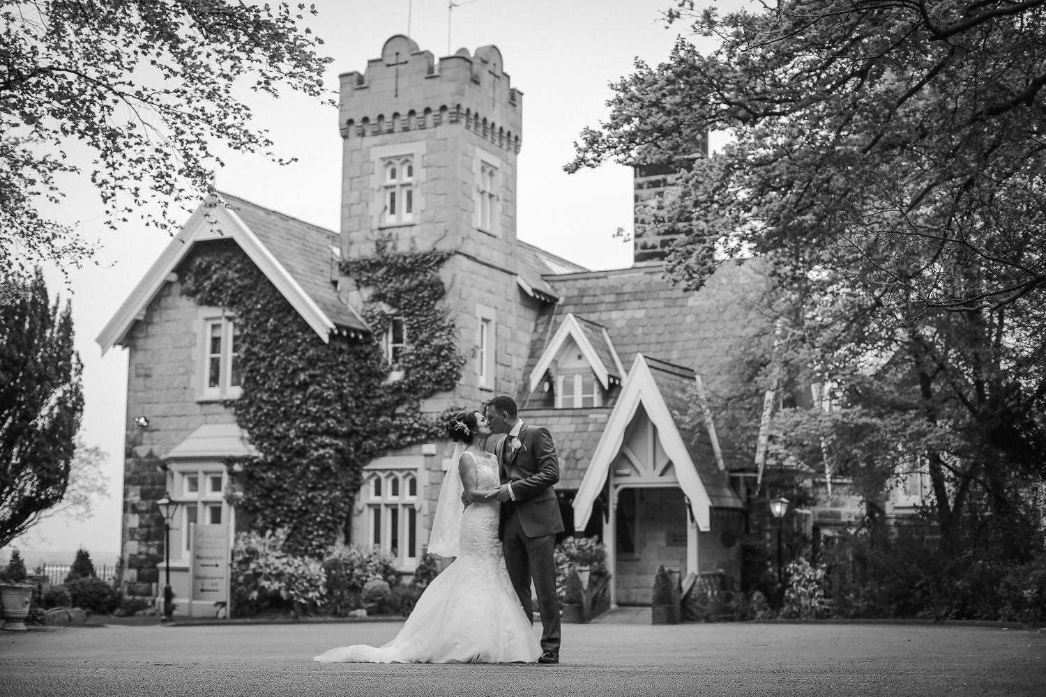 Black and white photo of bride and groom kissing in front of West Tower Top 10 wedding venues in Liverpool