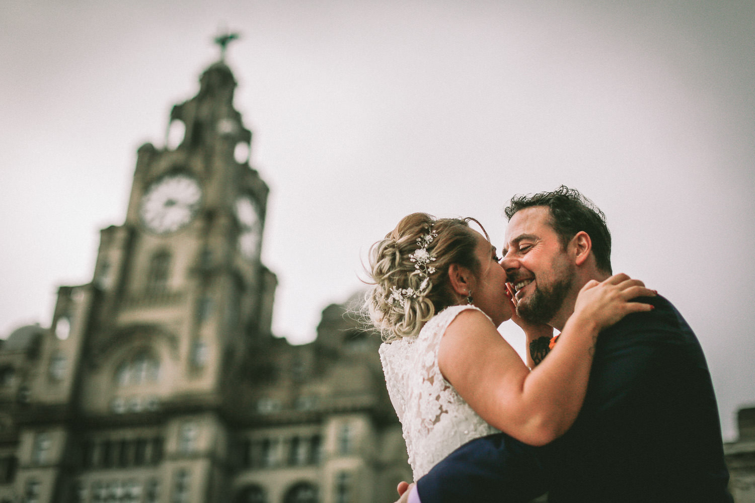 Bride and groom kissing in front of Royal Liver Building Top 10 wedding venues in Liverpool