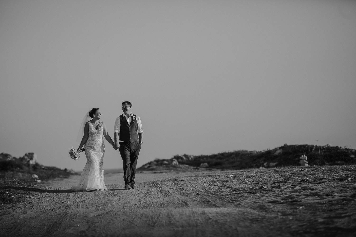 Bride and groom holding hands walking down dirt road in Paphos cyprus