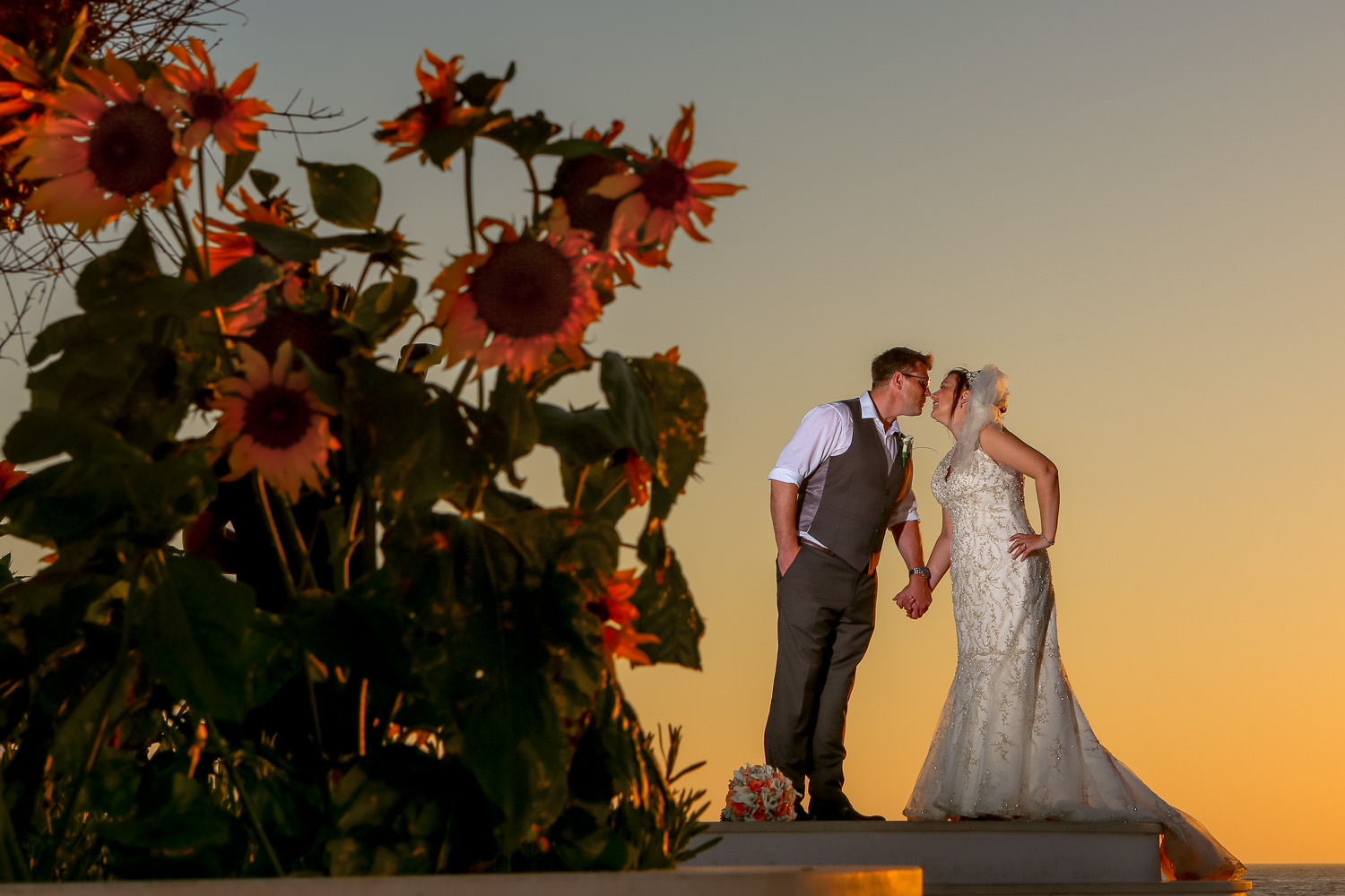 Alexander The Great Beach Hotel wedding photography. Bride and groom kissing at sunset next to sunflowers