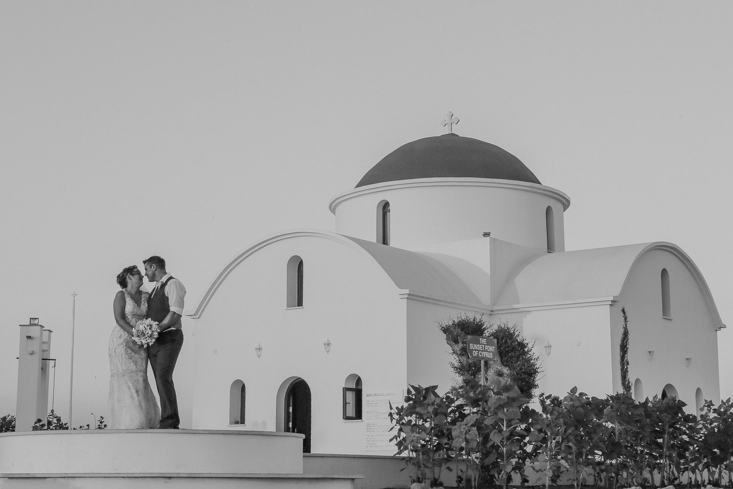 Black and white photo of bride and groom standing next to little chapel Paphos Cyprus