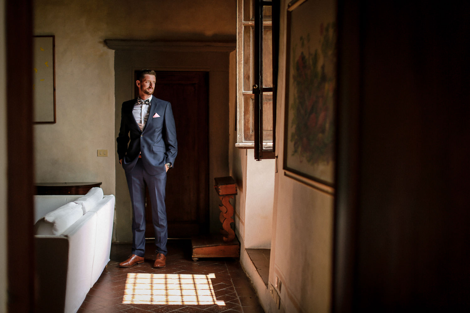 Groom waring blue suit standing in window for portrait