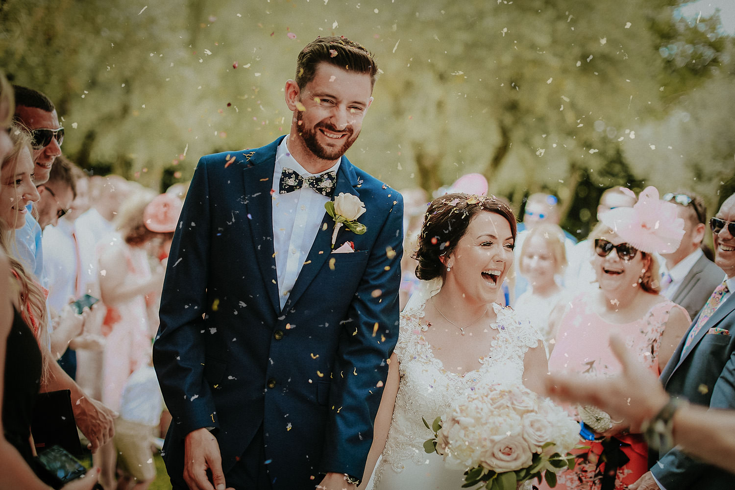 Bride and groom under confetti Castello di bibbione wedding photography Tuscany