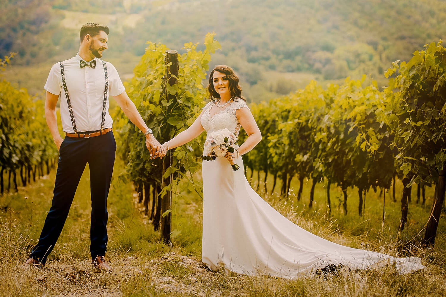 bride wearing maggie sottero holding grooms hand in fields in Tuscany