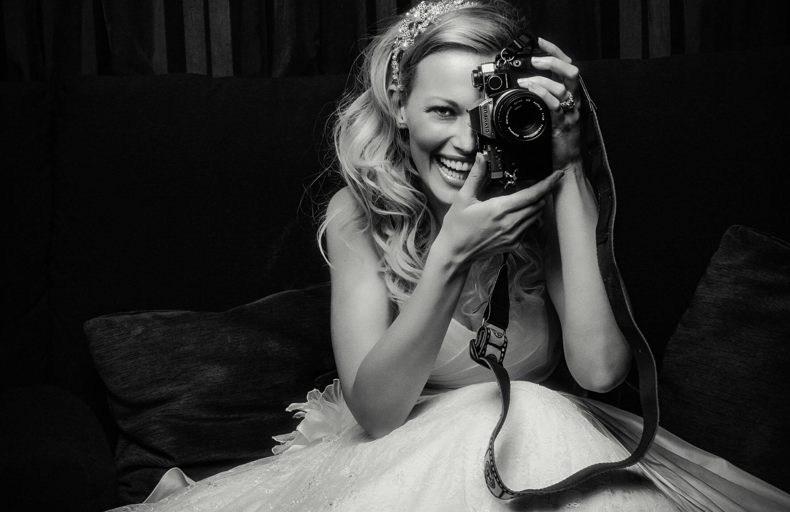 Black and white photo of bride taking photo with vintage camera