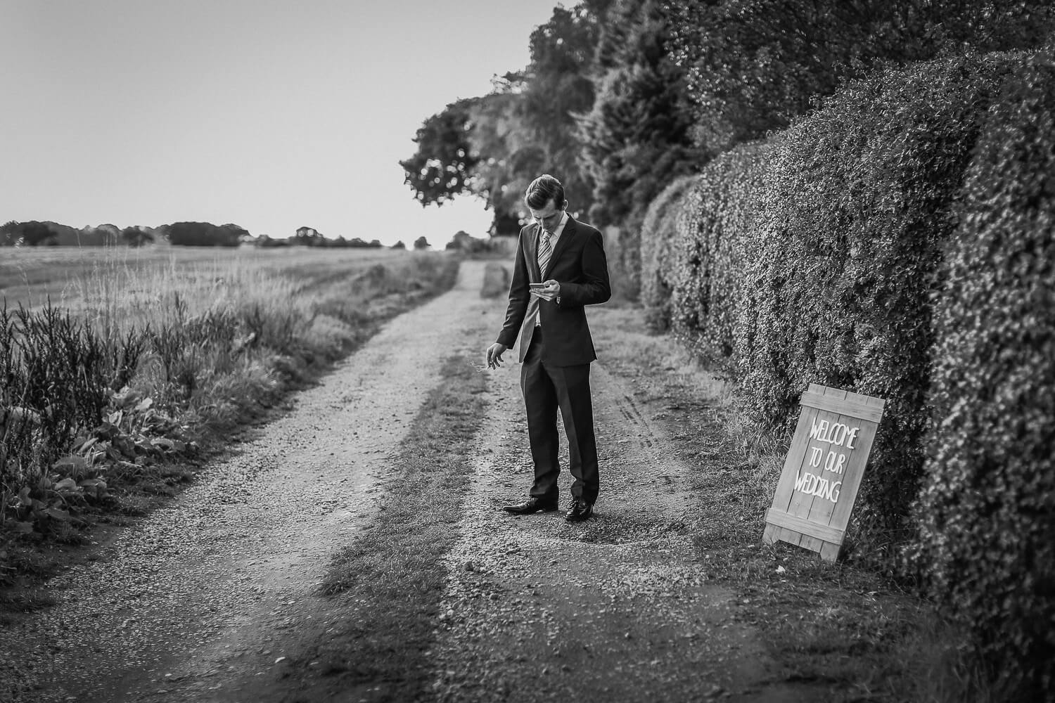 Black and white photo of Man standing in road smoking next to sign that reads welcome to our wedding Black and white photo of bride and groom family farm marquee wedding Ormskirk Lancashire Photographer
