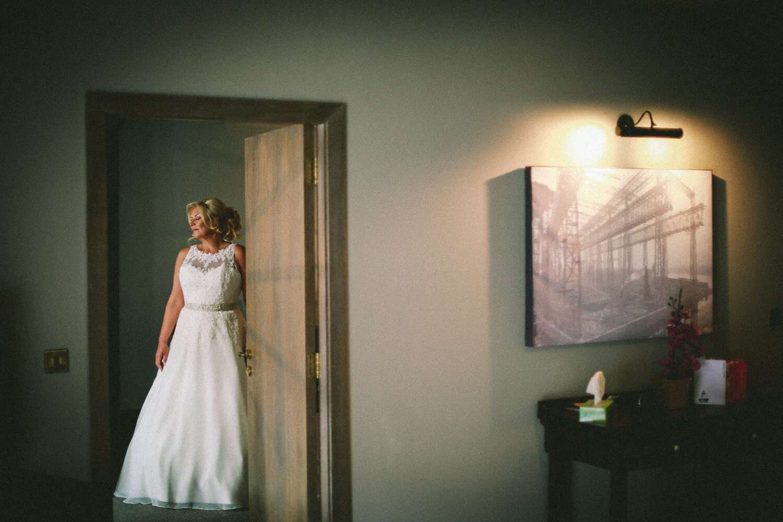 Bride on her own in doorway Titanic Hotel Wedding Liverpool.