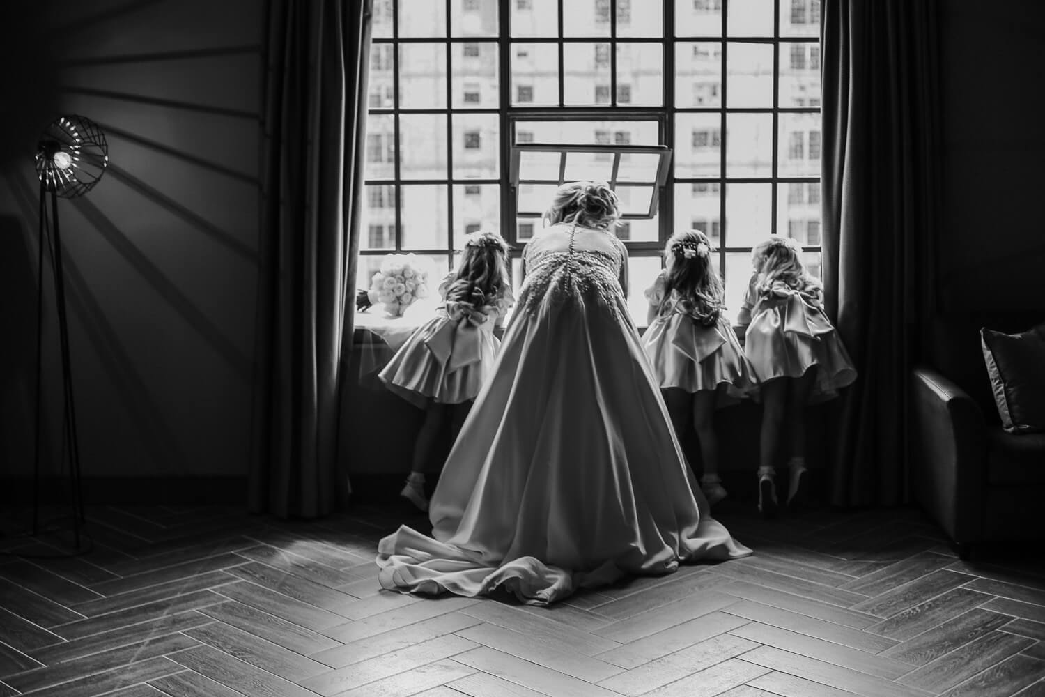Bride and flower girls looking out of window Titanic Hotel Wedding Liverpool.