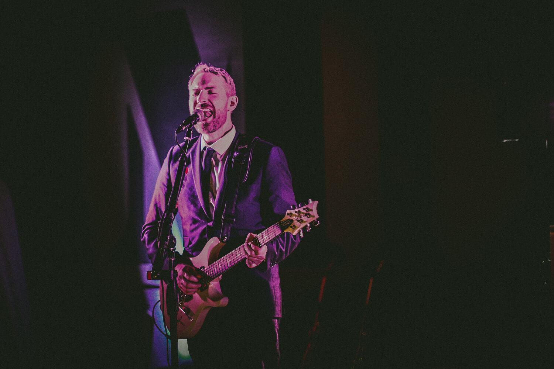 Man singing playing guitar Titanic Hotel Wedding Liverpool.