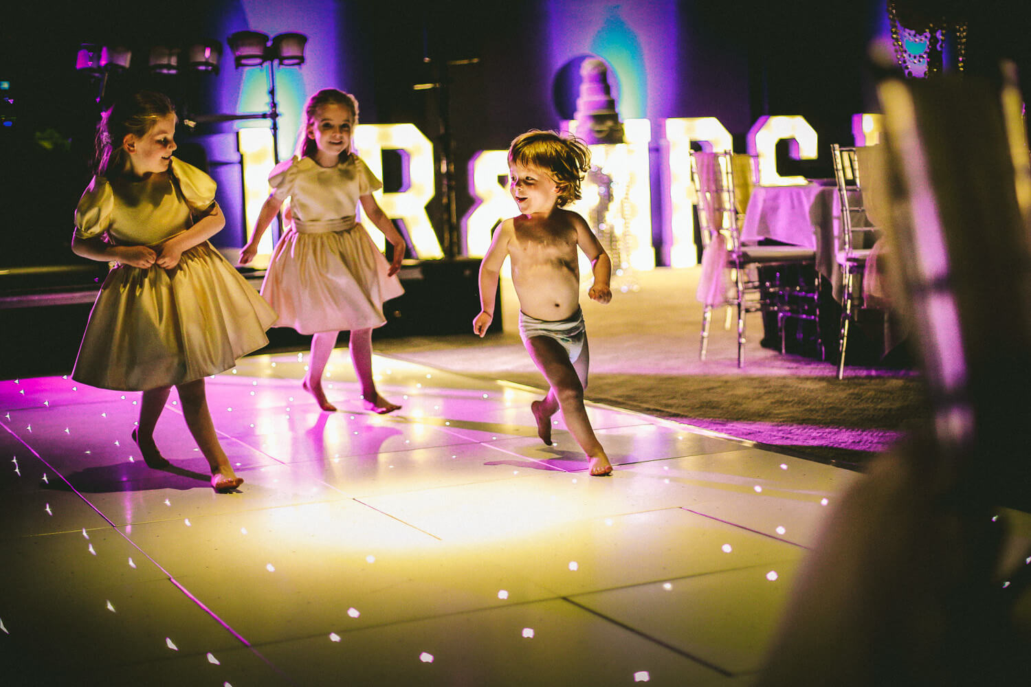 Flower girls chasing little boy in nappy on dance floor Titanic Hotel Wedding Liverpool.