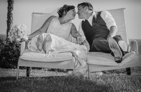Bride and groom kissing on sun loungers Alexander The Great Beach Hotel Cyprus wedding photography