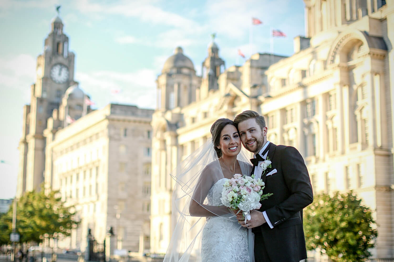 Cool portrait of bride and groom in front of Liver Building liverpool water front