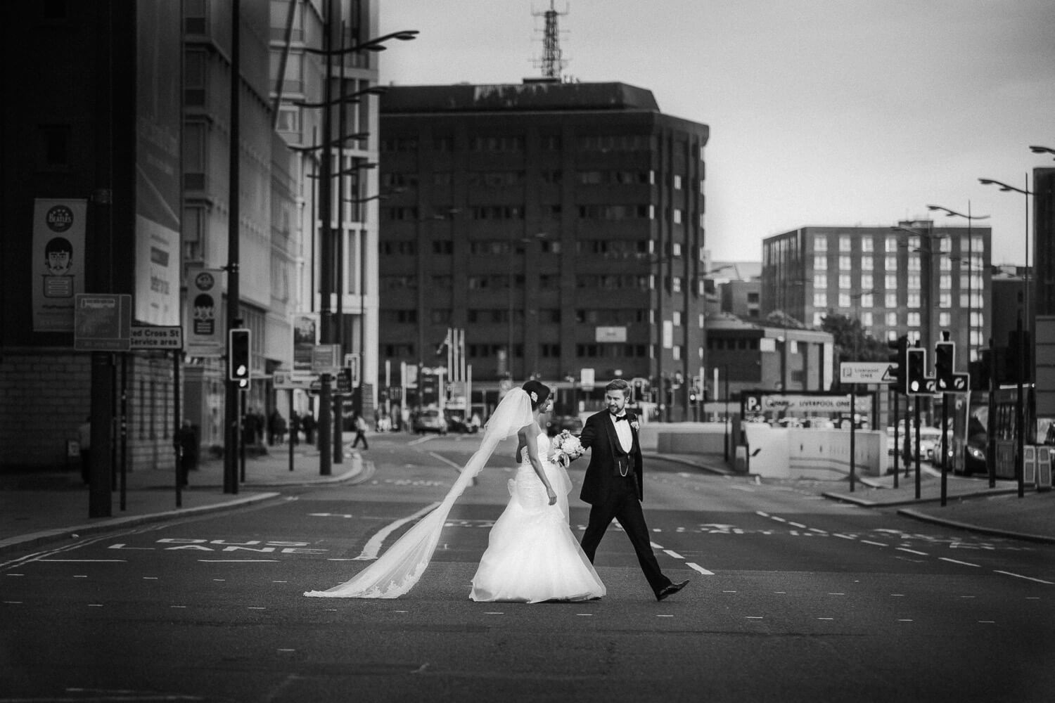 Bride and groom crossing busy Liverpool dock road on wedding day wearing Morilee wedding dress