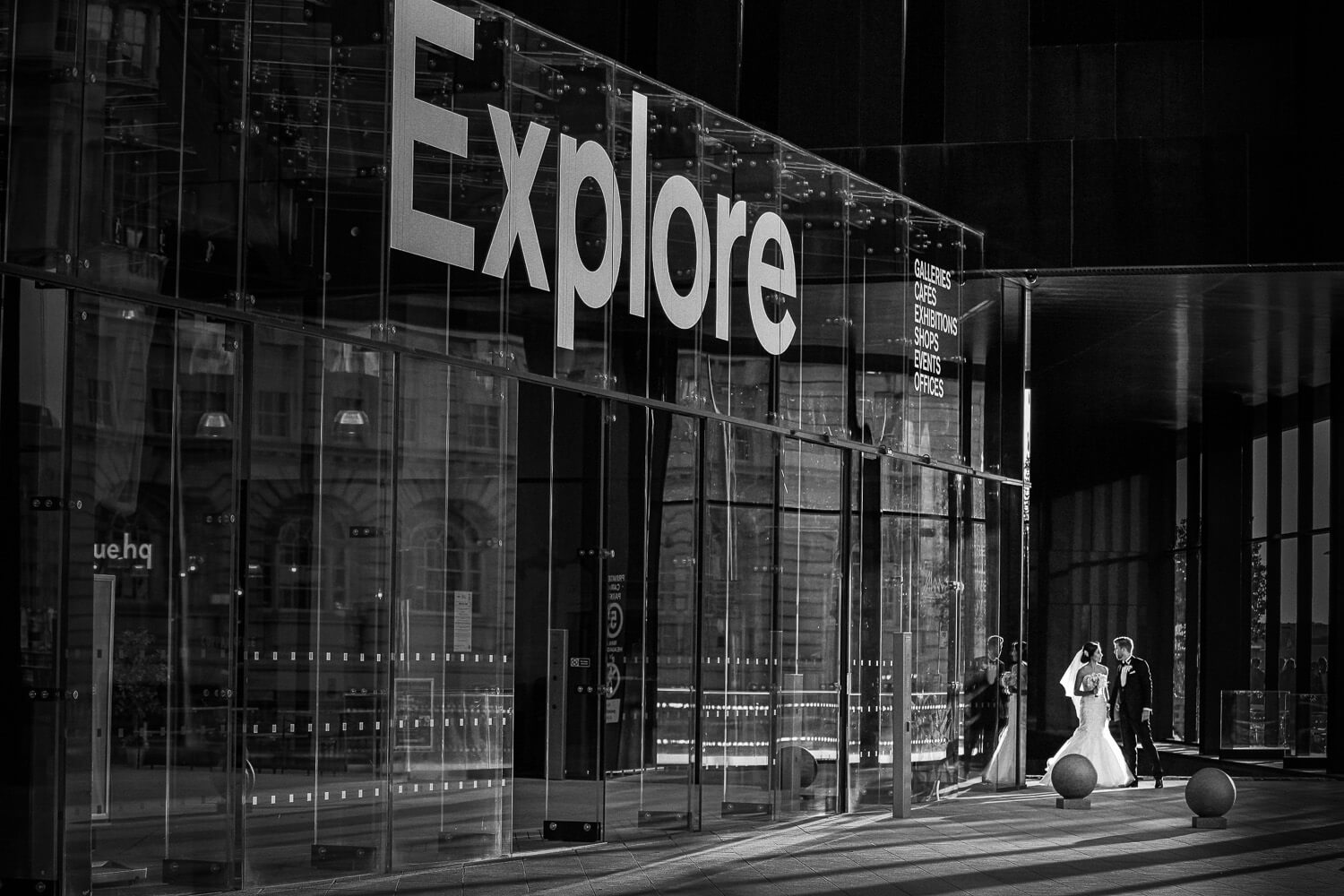 Bride and groom walking past words saying explore 30 James Street Liverpool wedding photography