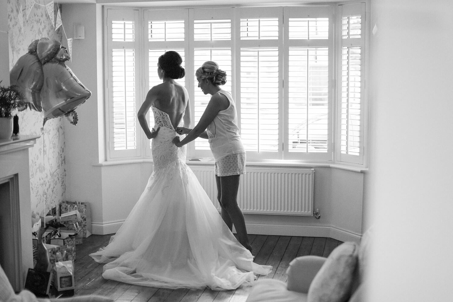 black and white photo of bridesmaid helping bride into her morilee wedding grown infant of window 30 James Street Liverpool wedding photography