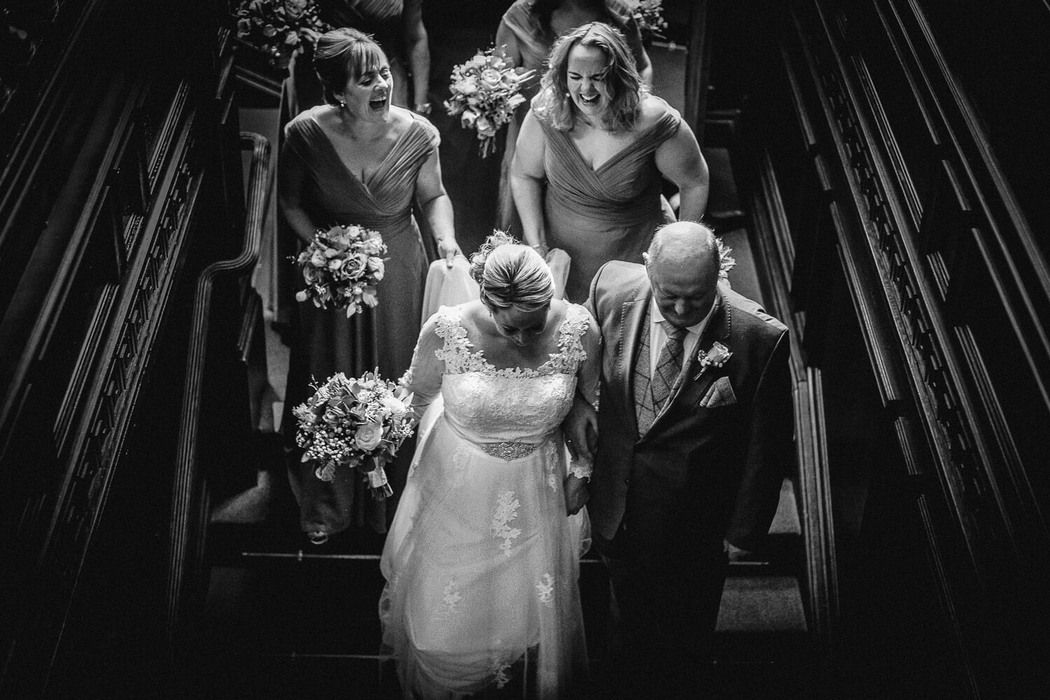 black and white photo of Bride dad and bridesmaids coming walking down stairs at Eaves Hall on wedding day