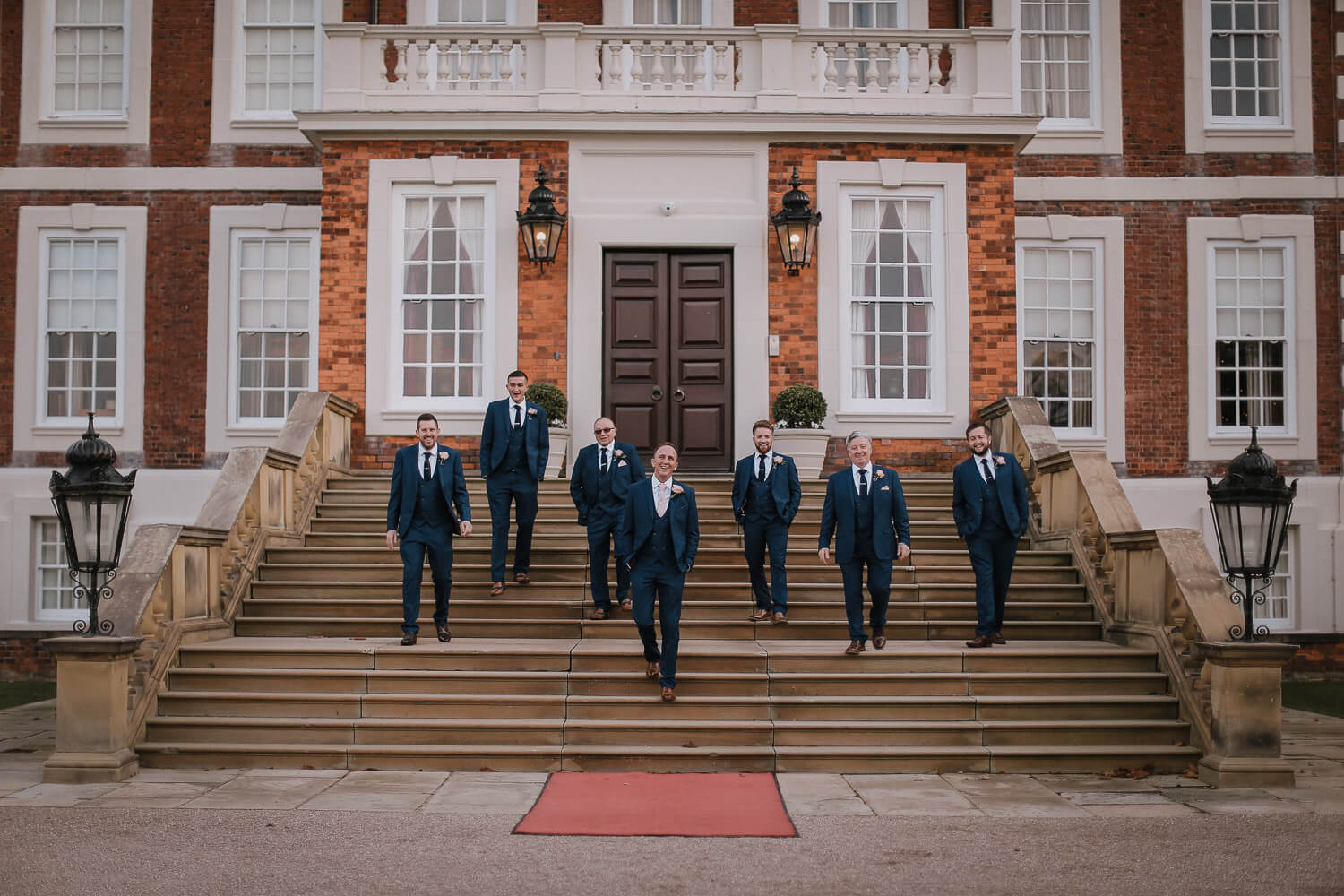 Groom and usher in blue suits on steps of Knowsley Hall