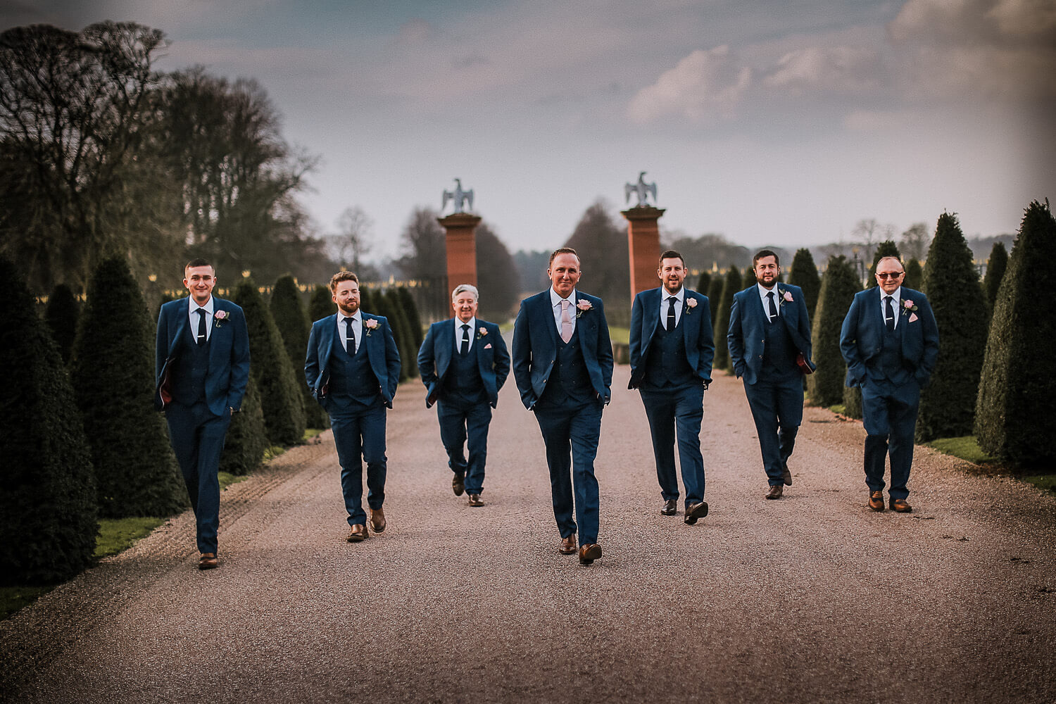 Groom and users walking in blue suit Knowsley Hall wedding photography