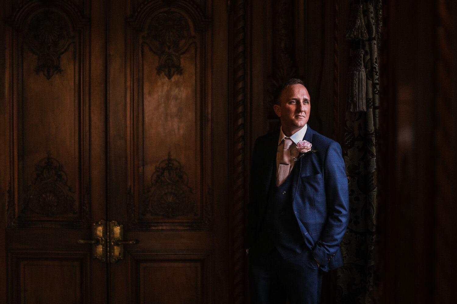 Portraits go groom wearing blue suit at Knowsley Hall wedding photography