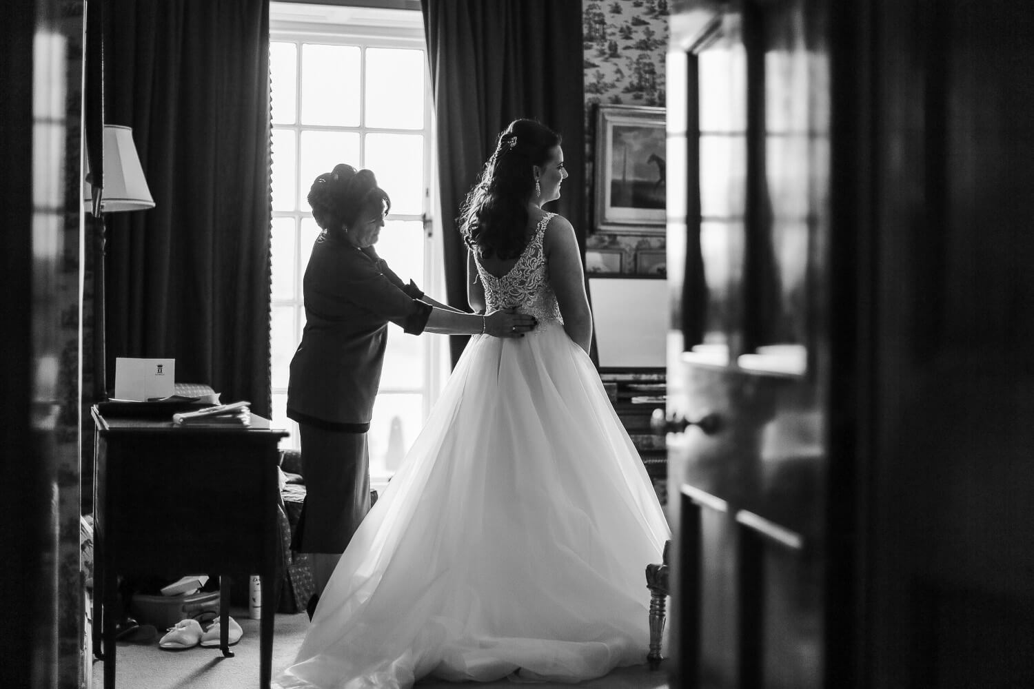 black and white photo shot through poor bride getting ready at Knowsley Hall