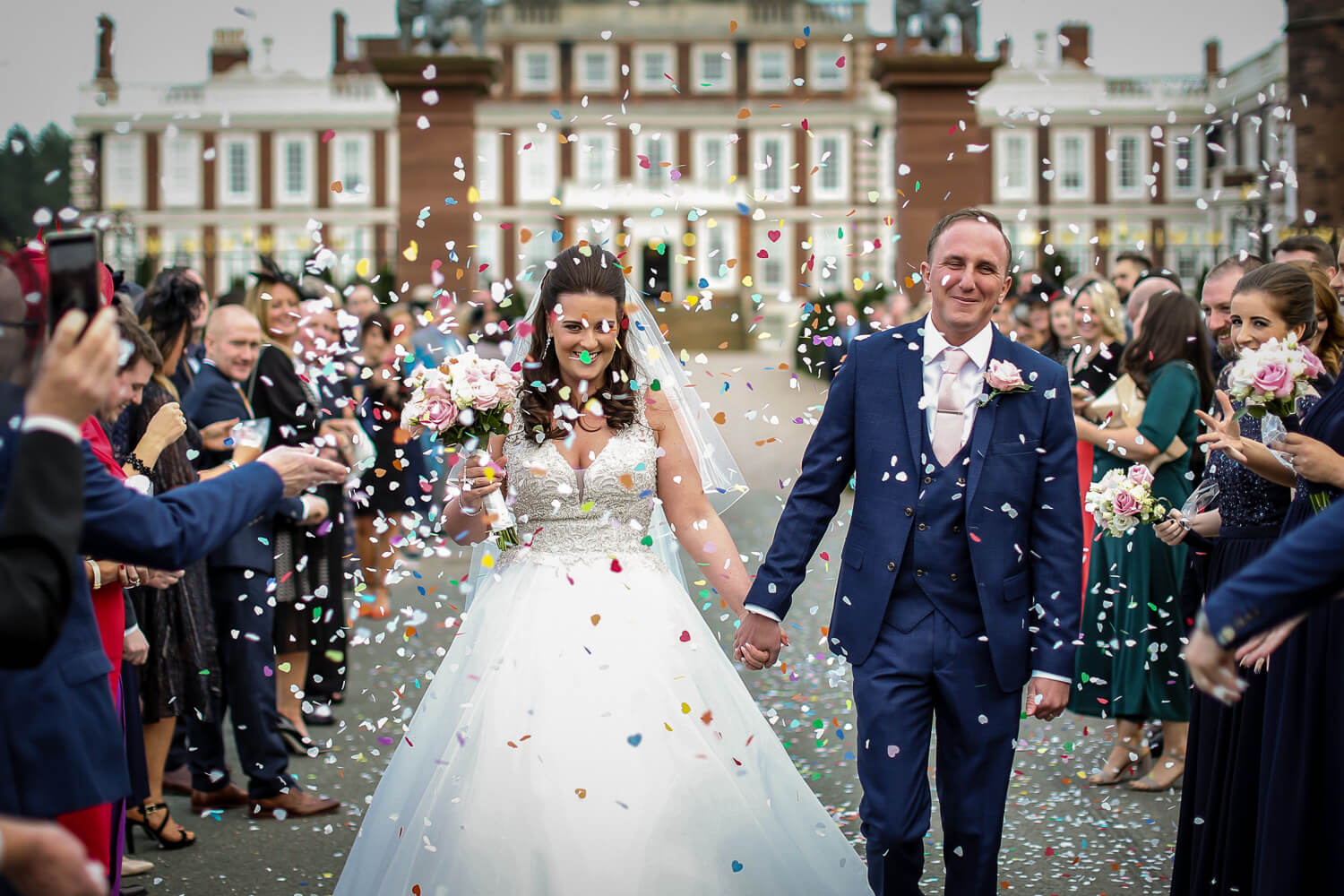 Knowsley Hall wedding photography bride and groom under confetti