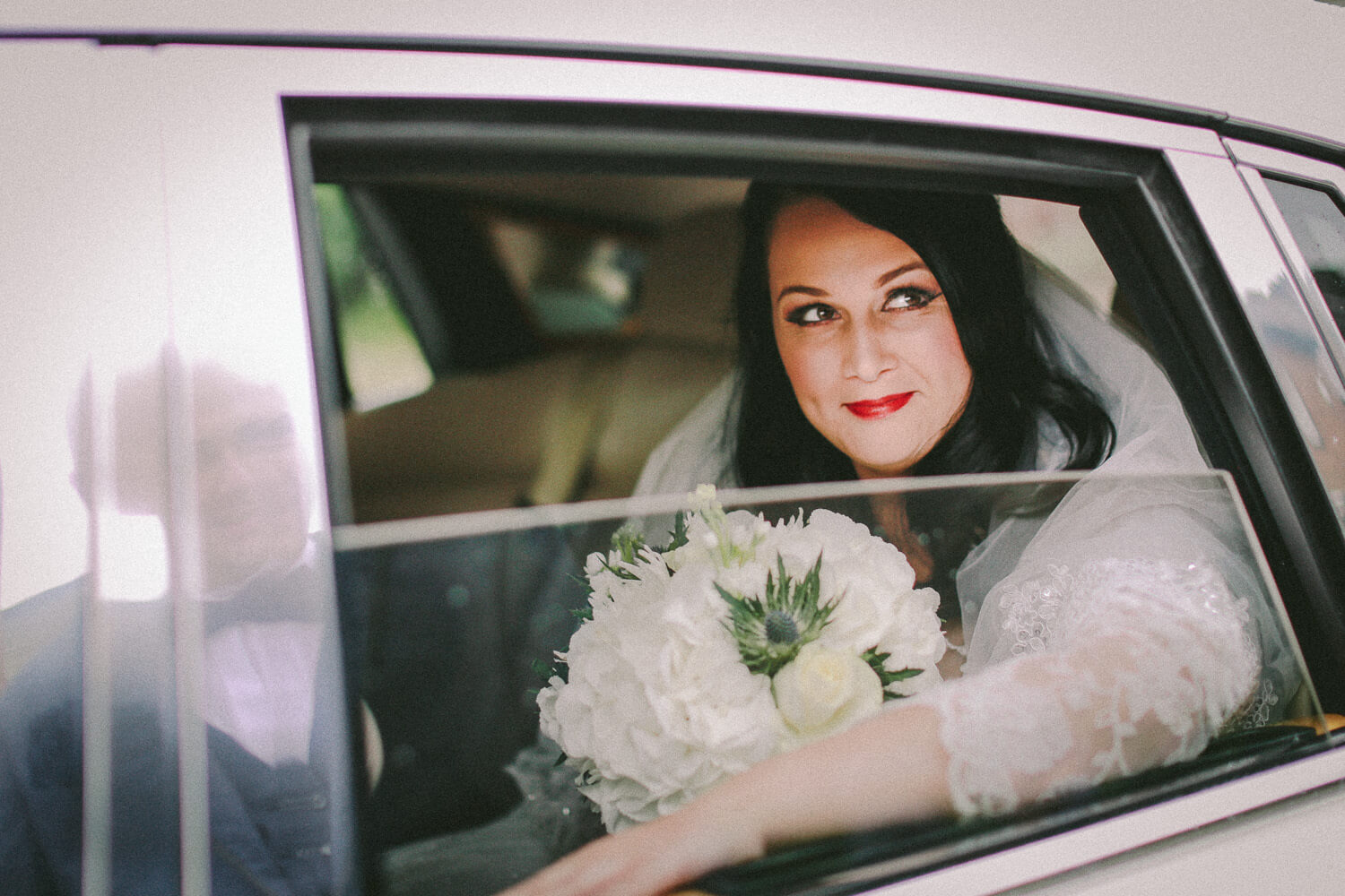 Photo of bride through Rolls Royce window pulling up at St Teresa's Church Liverpool