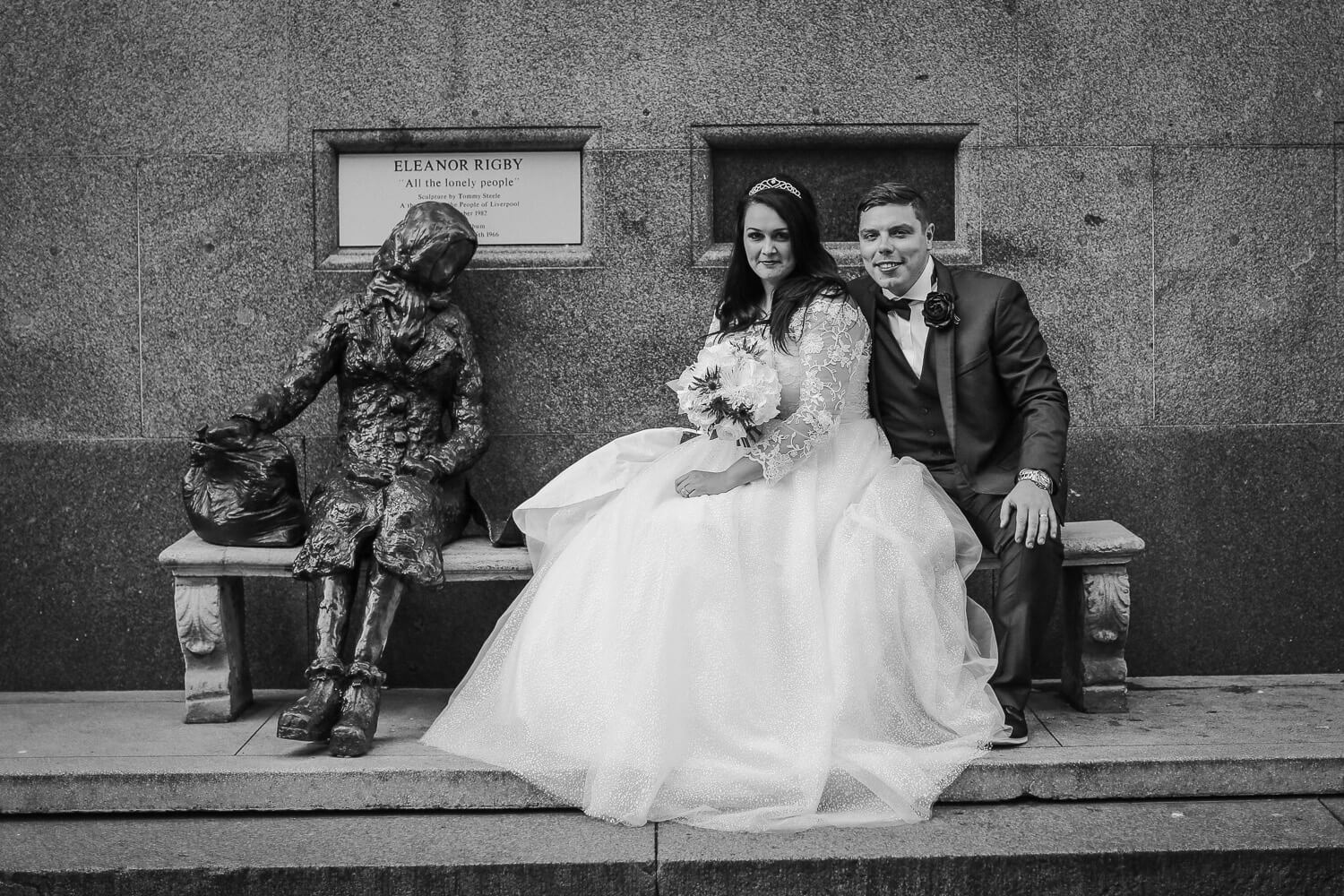 Bride and groom sitting with Eleanor Rigby statue Sir Thomas Hotel, Liverpool city wedding photographer