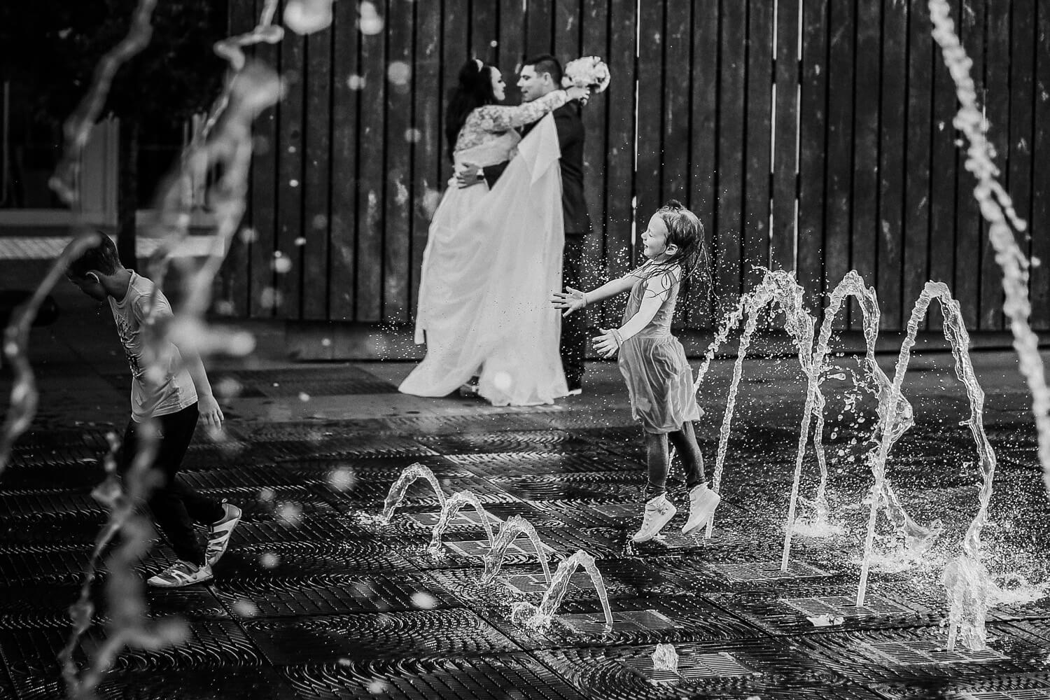 black and white photo of little girl playing in water fountain queens square with bride and groom in background