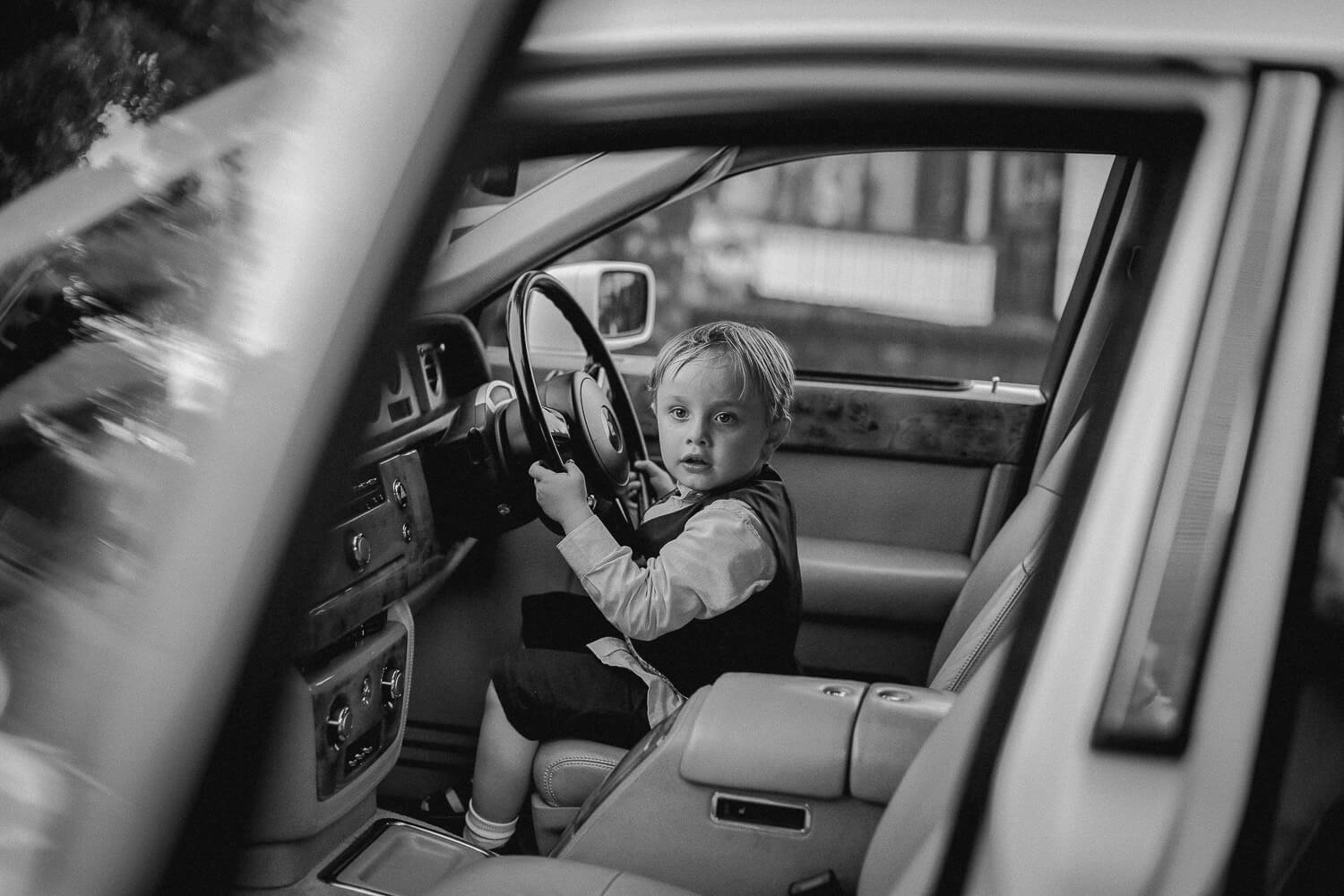 black and white photo of little boy playing in rolls royce wedding car