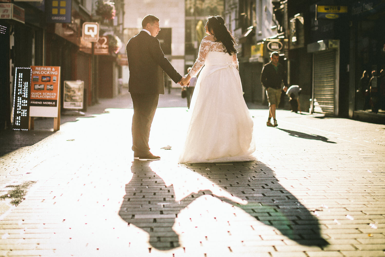 photo of shadow of bride and groom walking down street in liverpool