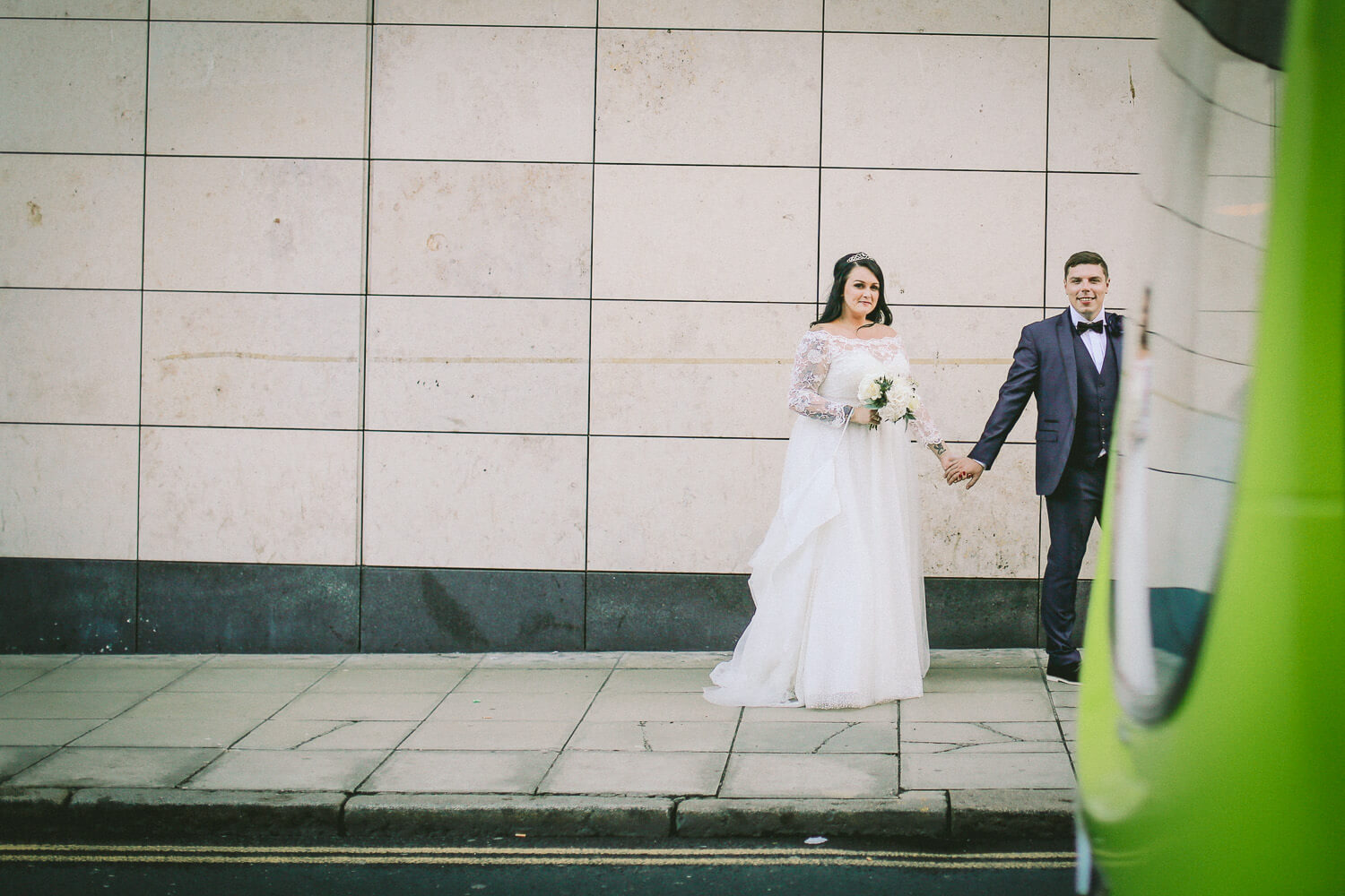 photo of bride and groom with bus going past Sir Thomas Hotel, Liverpool city wedding photographer