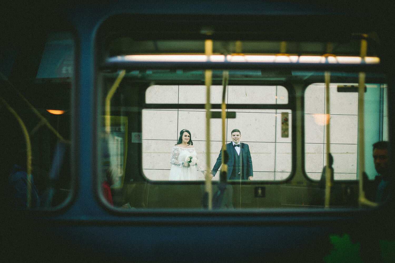 photo of bride and groom through bus window Sir Thomas Hotel, Liverpool city wedding photographer