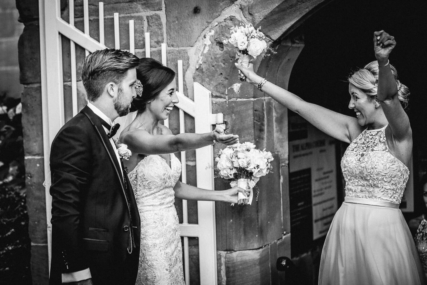 Excited bridesmaid congratulating bride and groom All saints church Liverpool