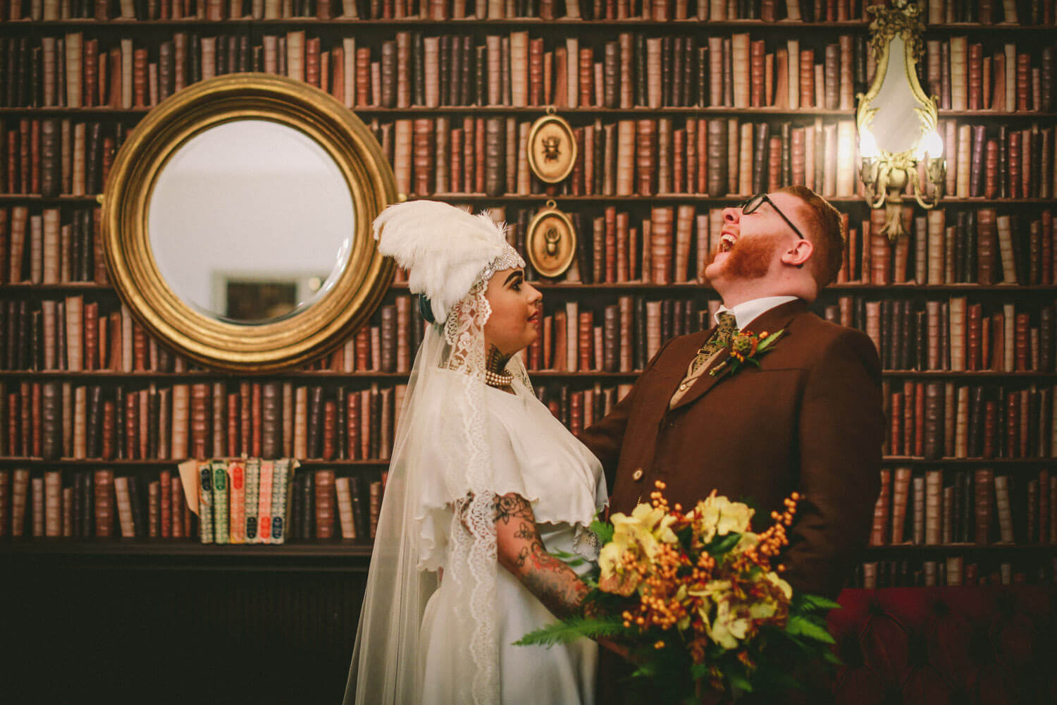 Vintage wedding groom laughing in front of books with bride in headwear